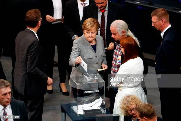 German Chancellor and leader of the Christian Democratic Union party, Angela Merkel casts her vote to elect the parliament leader during the first...