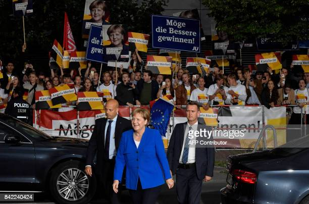 German Chancellor and leader of the conservative Christian Democratic Union party Angela Merkel files past supporters as she arrives for a televised...