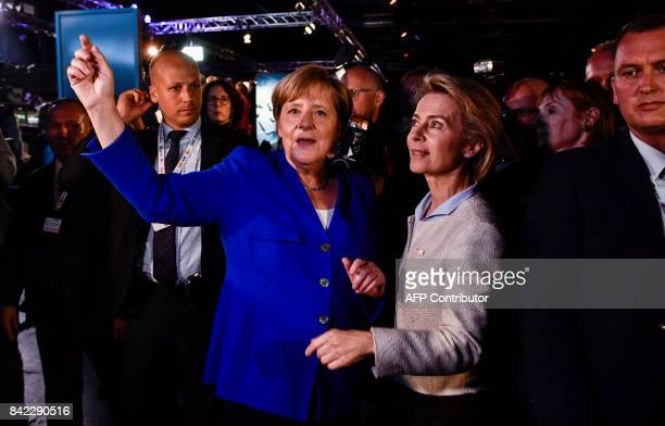 German Chancellor and leader of the conservative Christian Democratic Union party Angela Merkel gestures as she chats with German Defence Minister...