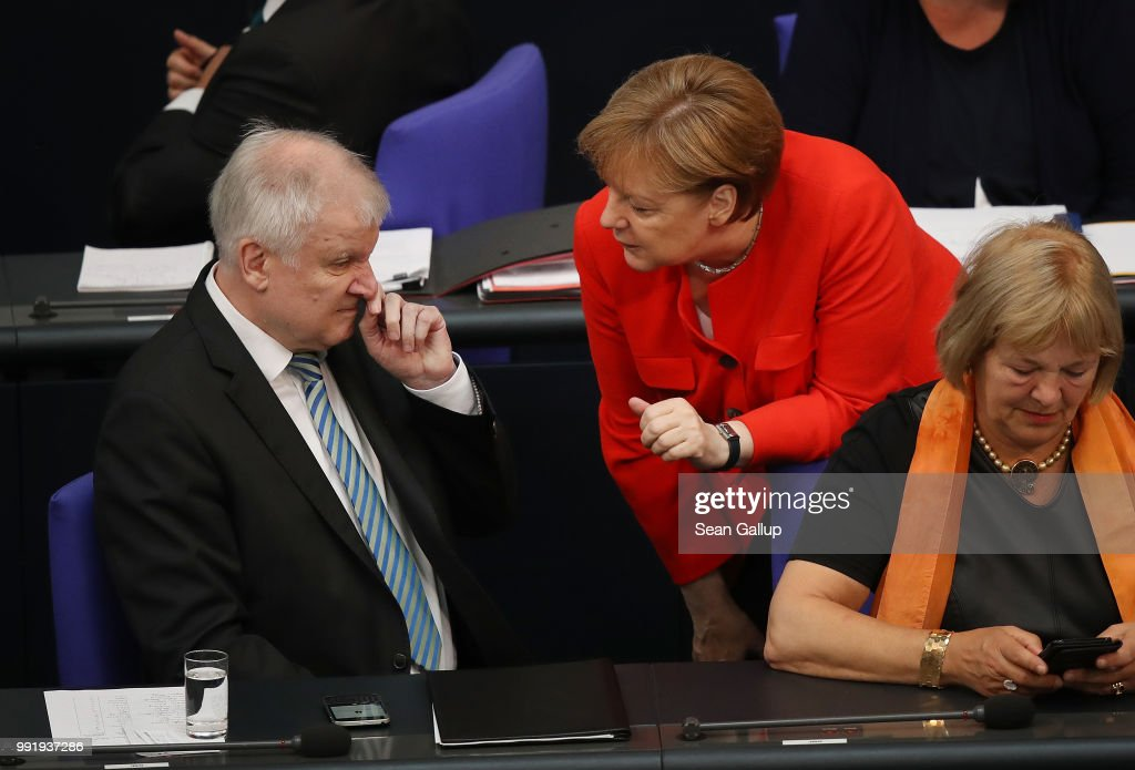 German Chancellor and leader of the German Christian Democratic Union (CDU) Angela Merkel and Interior Minister and leader of the CDU sister party, the Bavarian Social Union (CSU), Horst Seehofer, speak with one another at the last session of the Bundestag before the sumer break on July 5, 2018 in Berlin, Germany. Merkel and Seehofer recently reached a hard-wrung compromise over migration policy, though uncertainty remains over how the compromise will be implemented.
