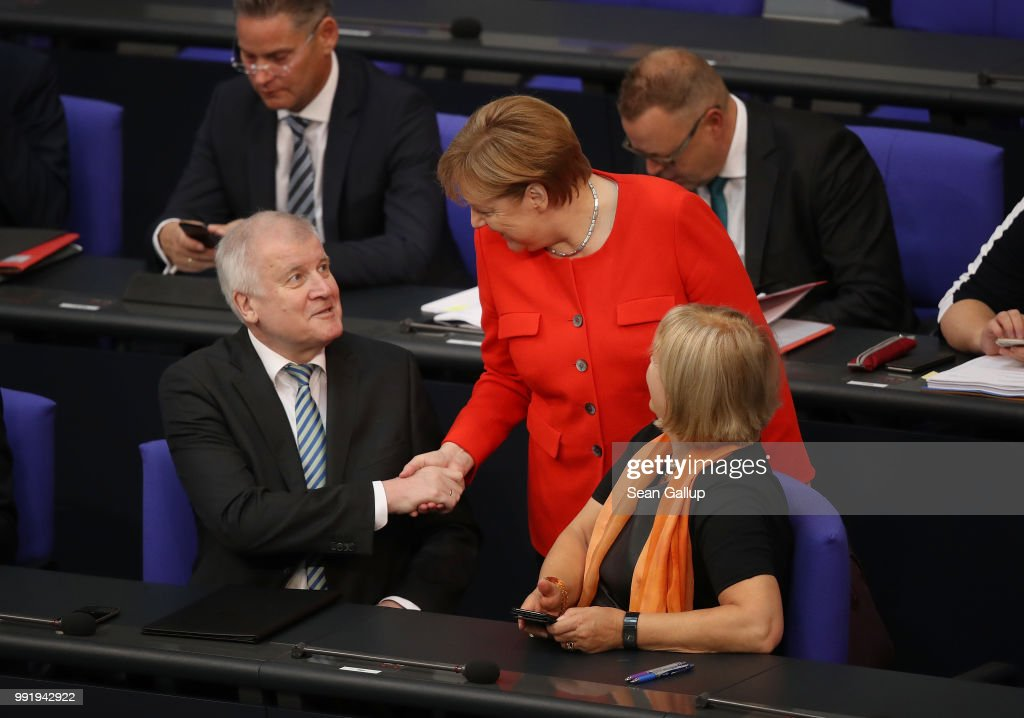 German Chancellor and leader of the German Christian Democratic Union (CDU) Angela Merkel greets Interior Minister and leader of the CDU sister party, the Bavarian Social Union (CSU), Horst Seehofer, upon her arrival at the last session of the Bundestag before the sumer break on July 5, 2018 in Berlin, Germany. Merkel and Seehofer recently reached a hard-wrung compromise over migration policy, though uncertainty remains over how the compromise will be implemented.