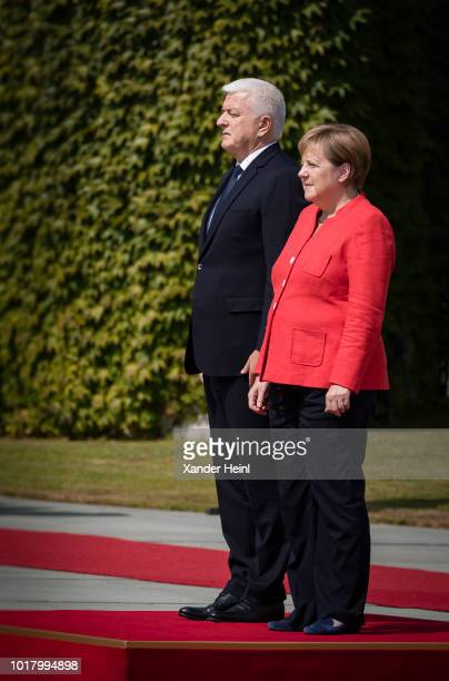 German Chancellor and leader of the German Christian Democrats Angela Merkel welcomes the Prime Minister of Montenegro Dusko Markovic with military...