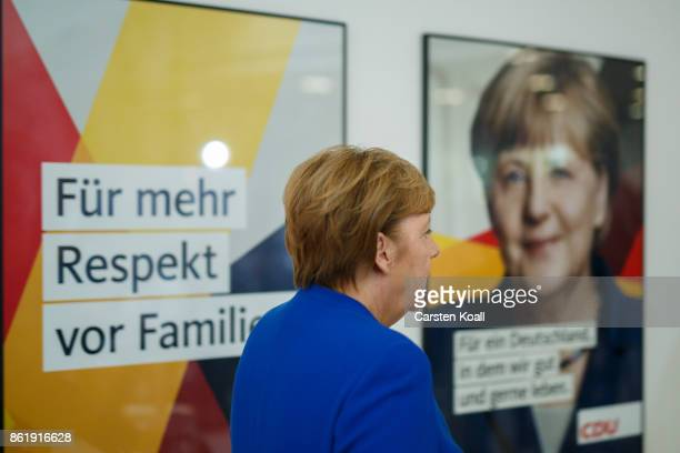 German Chancellor and leader of the German Christian Democrats Angela Merkel passes a picture of her after leaving a press conference together with...