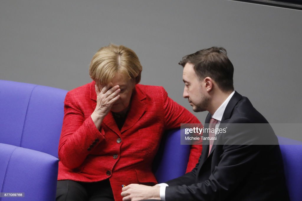 German Chancellor and leader of the German Christian Democrats (CDU) Angela Merkel speaks with Paul Ziemiak, chairman of the young associacion of the CDU party during the first session of the Bundestag, the German parliament, since the collapse of government coalition talks on November 21, 2017 in Berlin, Germany. Preliminary coalition talks, after over three weeks of arduous meetings, fell apart Sunday night, leaving Merkel confronted with two uncomfortable possibilities: attempt to run a minority government together with the German Greens Party or submit to new elections. Both would be a first at the federal level in post-World War II German history.