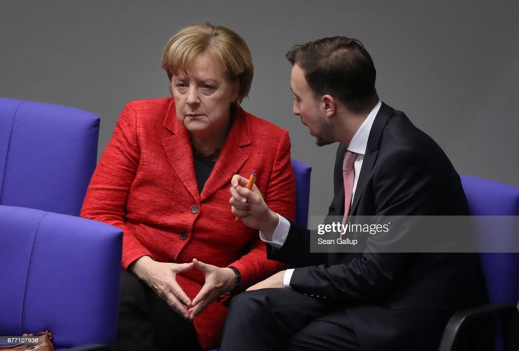 German Chancellor and leader of the German Christian Democrats (CDU) Angela Merkel (L) speaks with Paul Ziemiak, head of the Junge Union, the youth party of the CDU, as she attends the first Bundestag session since the collapse of government coalition talks on November 21, 2017 in Berlin, Germany. Preliminary coalition talks, after over three weeks of arduous meetings, fell apart Sunday night, leaving Merkel confronted with two uncomfortable possibilities: attempt to run a minority government together with the German Greens Party or submit to new elections. Both would be a first at the federal level in post-World War II German history.