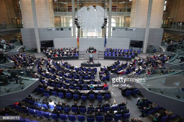 German Chancellor and leader of the German Christian Democrats Angela Merkel is seen on a monitor as she addresses the Bundestag during debates over...