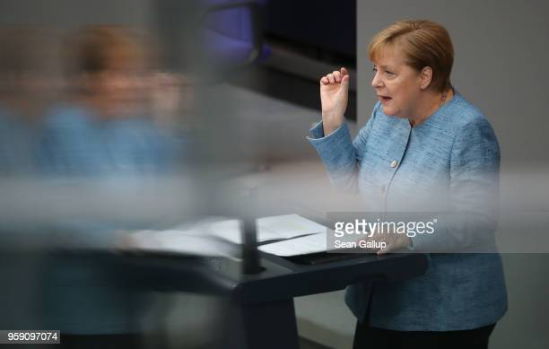 German Chancellor and leader of the German Christian Democrats Angela Merkel is reflected in glass as she addresses the Bundestag during debates over...
