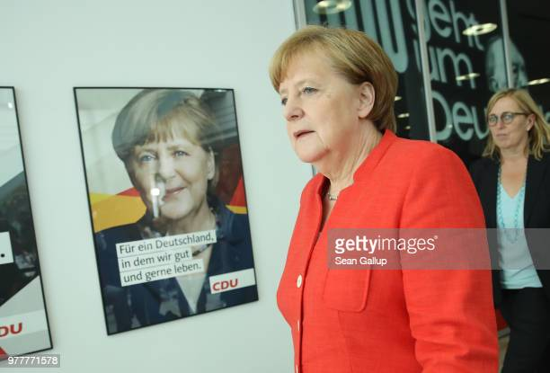 German Chancellor and leader of the German Christian Democrats Angela Merkel walks past an election campaign poster of herself as she arrives to...
