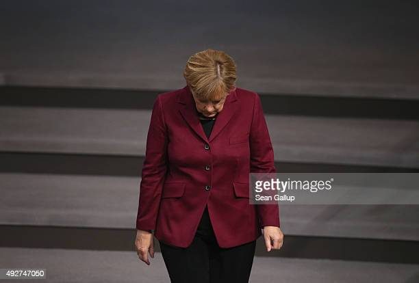 German Chancellor Angel Merkel walks into the plenary hall at the Bundestag during debates that centered on Germany's refugee policy on October 15...