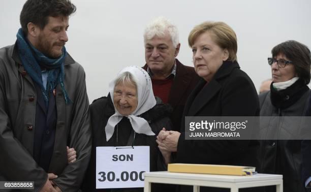 German Chancellor Angela Merkel accompanied by Argentine plastic artist Marcelo Brodsky and Madres de Plaza de Mayo cofounder Vera Jarach gestures...