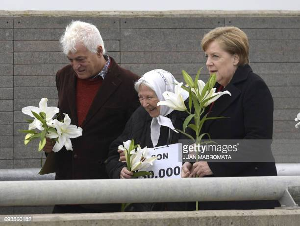 German Chancellor Angela Merkel accompanied by Argentine plastic artist Marcelo Brodsky and Madres de Plaza de Mayo cofounder Vera Jarach gestures...
