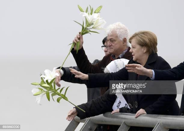 German Chancellor Angela Merkel accompanied by Argentine plastic artist Marcelo Brodsky and Madres de Plaza de Mayo cofounder Vera Jarach throws...
