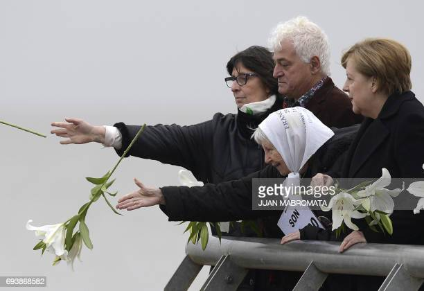 German Chancellor Angela Merkel accompanied by Argentine plastic artist Marcelo Brodsky and Madres de Plaza de Mayo cofounder Vera Jarach throws...