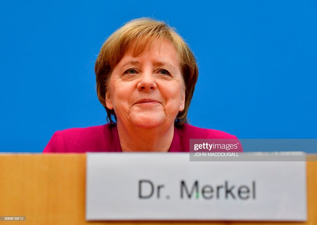 German Chancellor Angela Merkel addresses a press conference at the Federal Press Conference in Berlin, on March 12, 2018 prior to the signature of the chancellor's conservative CDU/CSU and the Social Democrats SPD's coalition contract for a new government. / AFP PHOTO / John MACDOUGALL