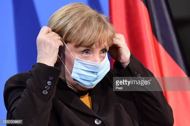 German Chancellor Angela Merkel adjusts her mask after a joint press conference with German Health Minister Jens Spahn at the chancellery on March...