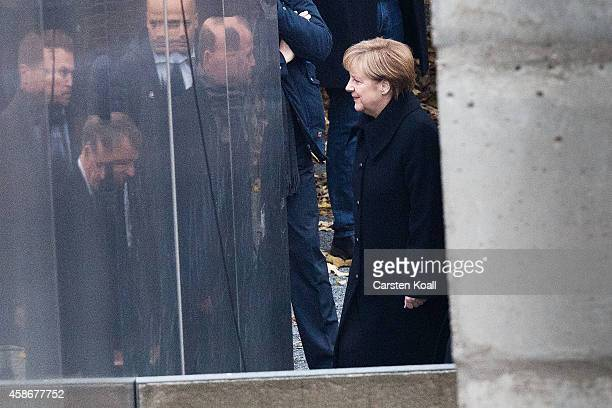 German Chancellor Angela Merkel after she placed flowers in between slats of the former Berlin Wall at the Berlin Wall Memorial at Bernauer Strasse...
