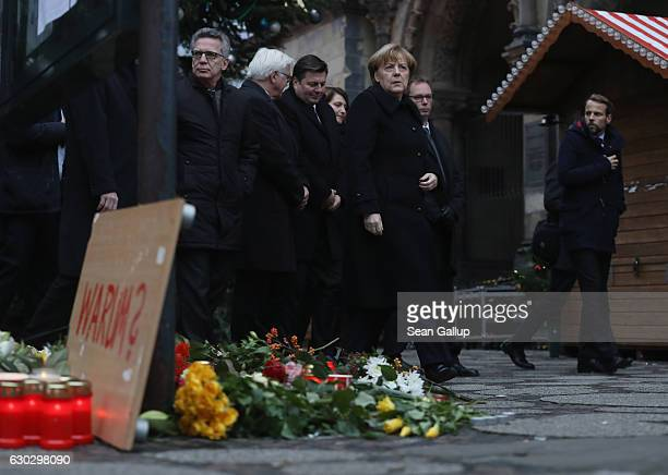 German Chancellor Angela Merkel along with Interior Minister Thomas de Maiziere and Foreign Minister FrankWalter Steinmeier depart after laying...