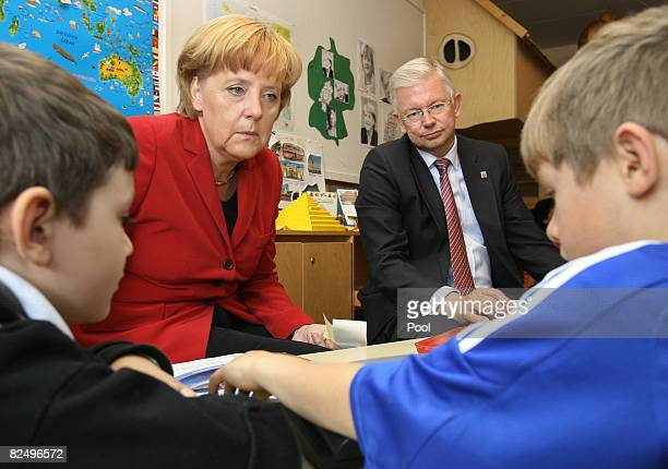 German Chancellor Angela Merkel and 2 governor of the German state of Hesse pose with children at the evangelic Friedensgemeinde kindergarten August...