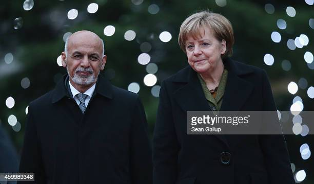 German Chancellor Angela Merkel and Afghan President Ashraf Ghani walk past a Chrismtas tree upon Ghani's arrival at the Chancellery on December 5,...