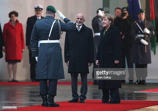 German Chancellor Angela Merkel and Afghan President Ashraf Ghani finish reviewing a guard of honour upon Ghani's arrival at the Chancellery on...