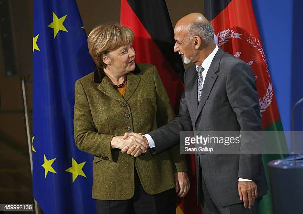 German Chancellor Angela Merkel and Afghan President Ashraf Ghani depart after speaking to the media following talks at the Chancellery on December 5...