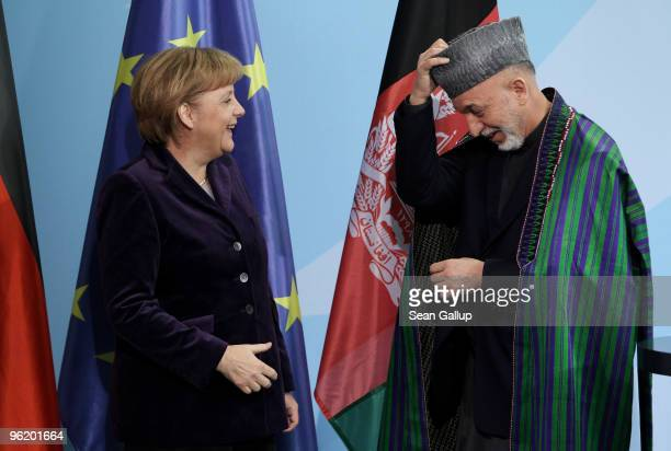 German Chancellor Angela Merkel and Afghan President Hamid Karzai depart after speaking to the media after talks at the Chancellery on January 27,...