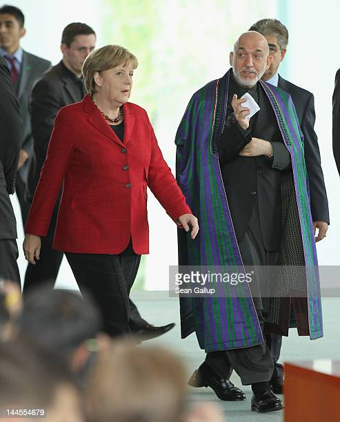 German Chancellor Angela Merkel and Afghan President Hamid Karzai arrive to sign agreements on the future role of Germany in Afghanistan on May 16,...