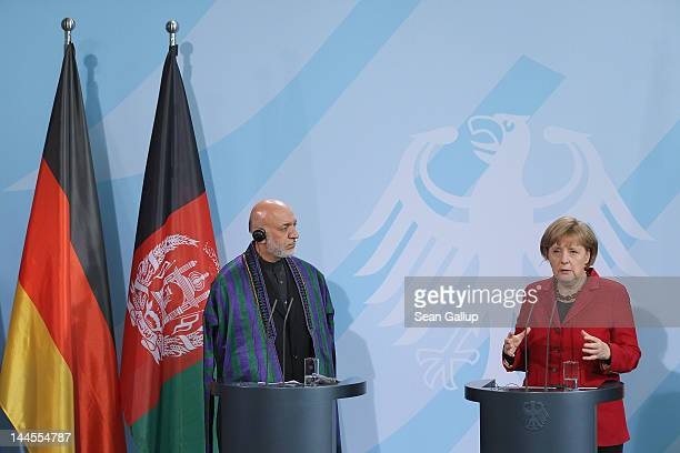 German Chancellor Angela Merkel and Afghan President Hamid Karzai speak to the media after signing agreements on the future role of Germany in...