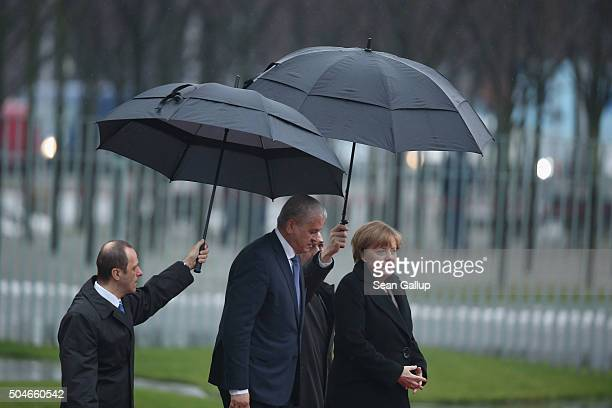German Chancellor Angela Merkel and Algerian Prime Minister Abdelmalek Sellal walk under umbrellas as they prepare to review a guard of honour upon...