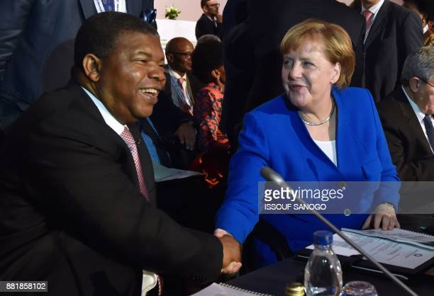German Chancellor Angela Merkel and Angolan President Joao Lourenco shake hands as they attend the 5th African Union European Union summit in Abidjan...