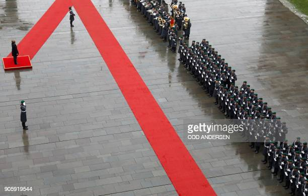 German Chancellor Angela Merkel and Austria's new Chancellor Sebastian Kurz inspect a military honor guard during a welcoming ceremony at the...