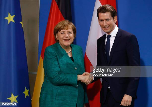 German Chancellor Angela Merkel and Austria's new Chancellor Sebastian Kurz shake hands after giving a joint press conference at the Chancellery in...
