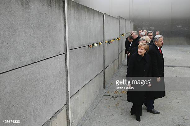 German Chancellor Angela Merkel and Berlin Mayor Klaus Wowereit depart after placing flowers in between slats of the former Berlin Wall at the Berlin...