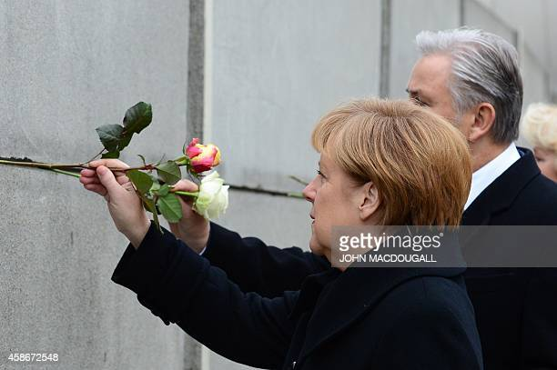 German Chancellor Angela Merkel and Berlin Mayor Klaus Wowereit put roses in a preserved segment of the Berlin Wall during the commemorations to mark...