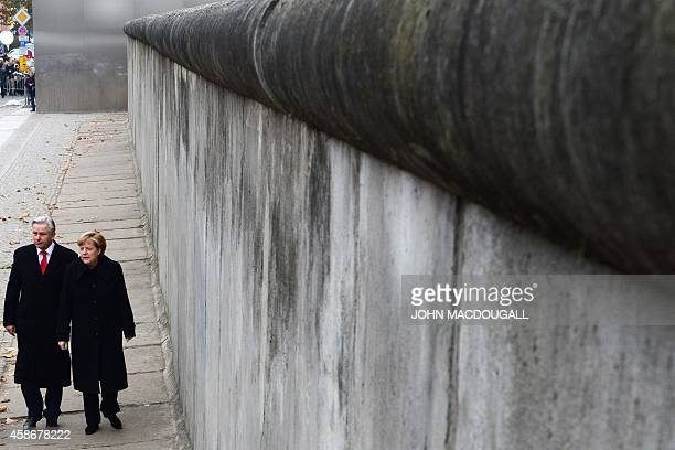 German Chancellor Angela Merkel and Berlin Mayor Klaus Wowereit walk by a preserved segment of the Berlin Wall during commemorations to mark the 25th...