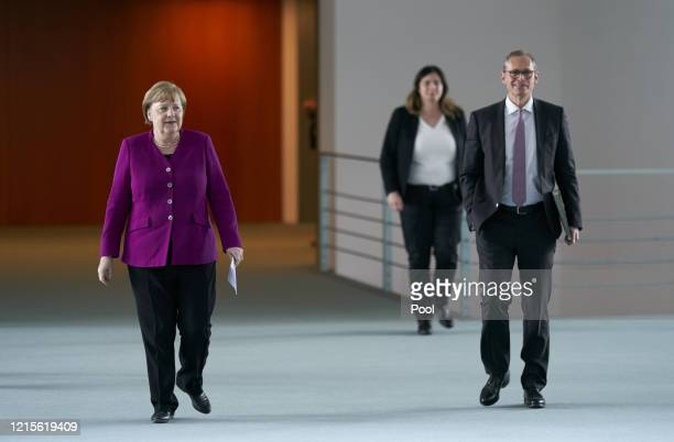 German Chancellor Angela Merkel and Berlin mayor Michael Mueller arrive to speak to the media following a teleconferenced meeting with leaders of...
