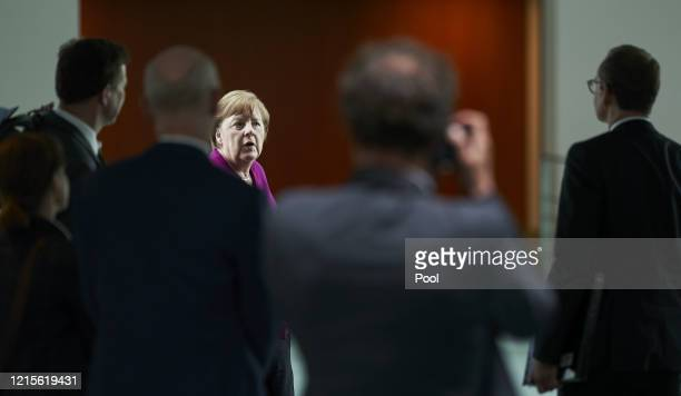 German Chancellor Angela Merkel and Berlin mayor Michael Mueller speak to the media following a teleconferenced meeting with leaders of Germany's...
