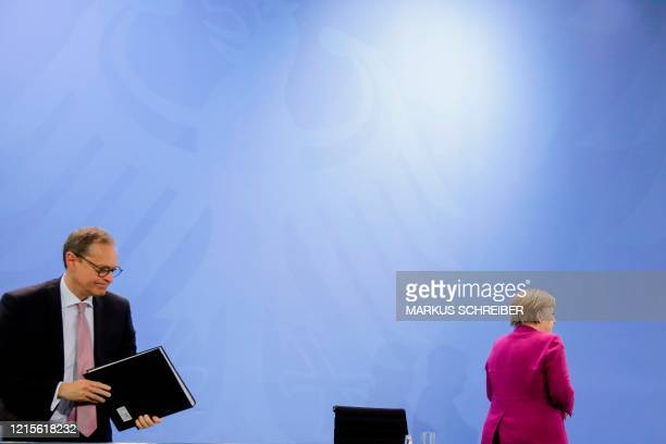 German Chancellor Angela Merkel and Berlin's Mayor Michael Mueller leave after a briefing with the media following a meeting of former East German...
