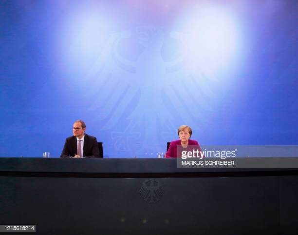 German Chancellor Angela Merkel and Berlin's Mayor Michael Mueller brief the media after a meeting of former East German state governors at the...
