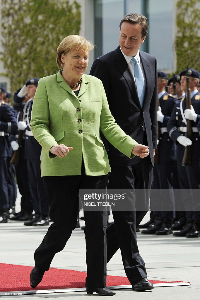 German Chancellor Angela Merkel and British Prime Minister David Cameron share a joke as they inspect an honour guard at the Chancellery in Berlin on May 21, 2010. Cameron is on his first visit to Germany since becoming prime minister.