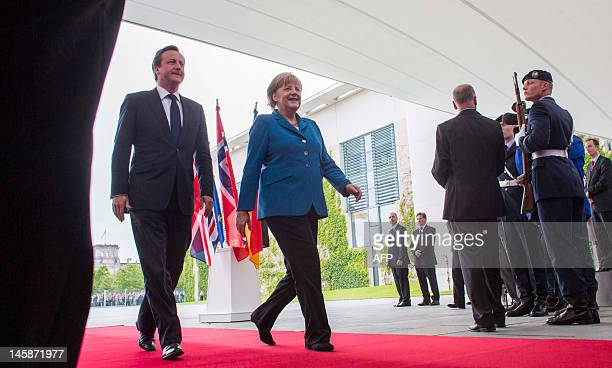 German Chancellor Angela Merkel and British Prime Minister David Cameron make their way prior to a debate with about 100 students from 16 countries...