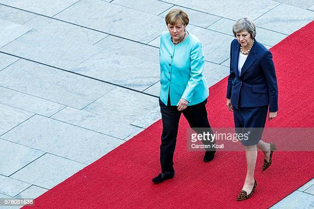 German Chancellor Angela Merkel and British Prime Minister Theresa May walk on a red carpet while reviewing a guard of honor upon May's arrival at...