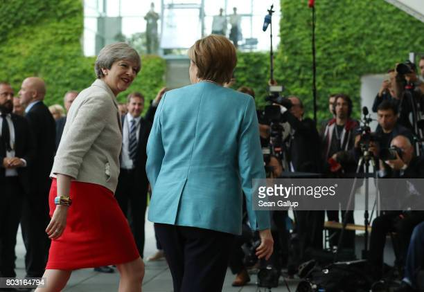 German Chancellor Angela Merkel and British Prime Minister Theresa May walk into the Chancellery for bilateral talks prior to a meeting of European...