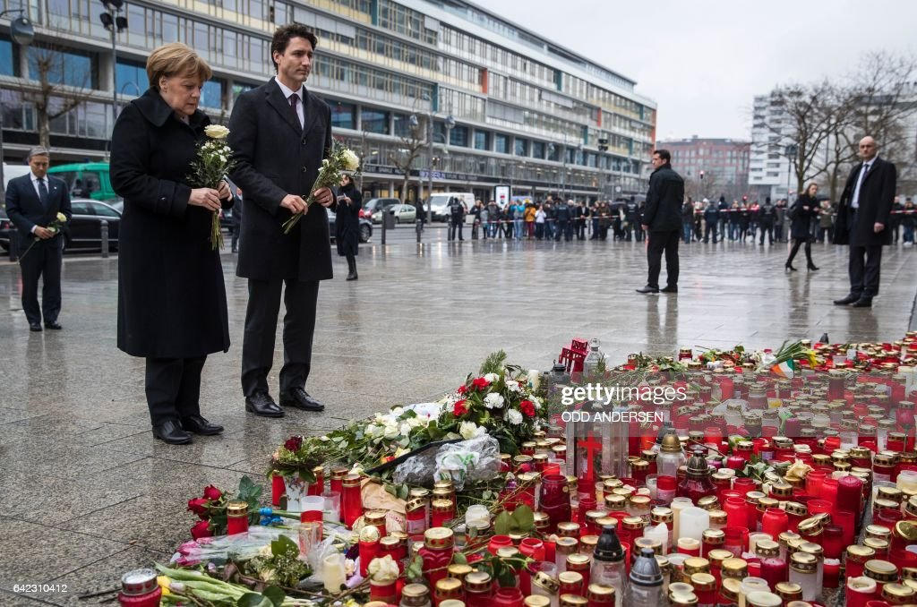 German Chancellor Angela Merkel (L) and Canadian prime minister Justin Trudeau place flowers at a memorial to the victims of the Breitscheidplatz Christmas market attack near the Kaiser-Wilhelm-Gedaechtniskirche (Kaiser Wilhelm Memorial Church) in Berlin on February 17, 2017. On December 19, 2016, suspected jihadist attacker Tunisian Anis Amri ploughed a hijacked truck into a Berlin Christmas market, killing 12 people, including the vehicle's registered driver. / AFP / Odd ANDERSEN