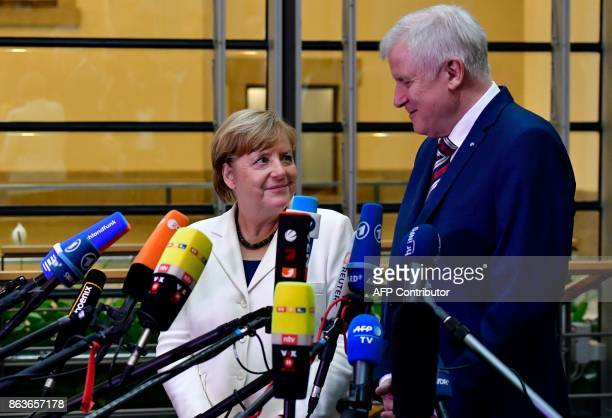 German Chancellor Angela Merkel and Chairman of the Christian Social Union Horst Seehofer make a statement as members of the delegations of the...