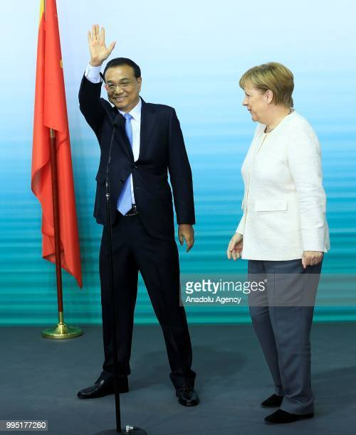German Chancellor Angela Merkel and Chinese Premier Li Keqiang hold a press conference pose for a photo with officials as they attend a presentation...