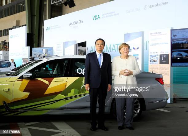 German Chancellor Angela Merkel and Chinese Premier Li Keqiang pose for a photo as they attend a presentation on autonomous driving at the Tempelhof...