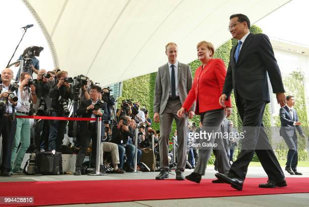 German Chancellor Angela Merkel and Chinese Premier Li Keqiang walk past photographers upon Li's arrival at the Chancellery on July 9 2018 in Berlin...