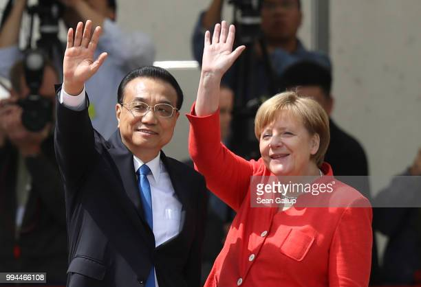 German Chancellor Angela Merkel and Chinese Premier Li Keqiang wave towards gathered supporters of the Chinese government after the two leaders...