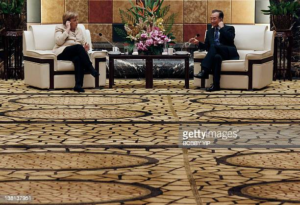 German Chancellor Angela Merkel and Chinese Premier Wen Jiabao adjust their earphones at a meeting with German and Chinese businessmen during her...